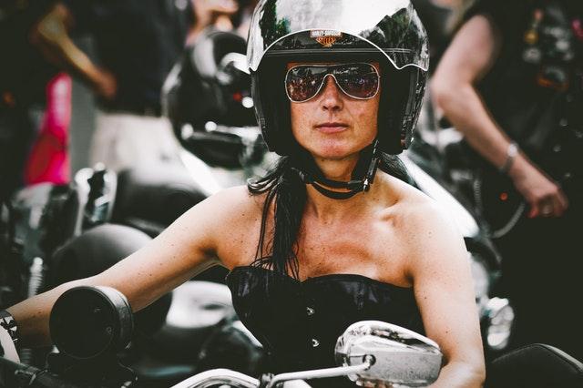 Žena v čiernom korzete, so slnečnými okuliarmi a  čiernou prilbou na hlave sedí na motorke