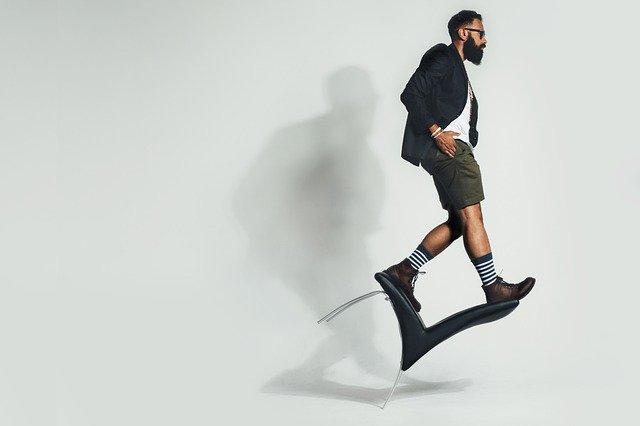 Muž v krátkych nohaviciach stojí na stoličke