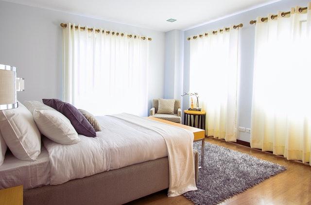 Manželská posteľ v spálni s veľkými oknami